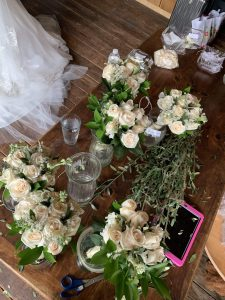Bouquets of white roses and greenery on the wood table in the bridal backstage area