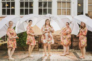 Bridal party posing with umbrellas